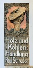 Fassadenbeschriftung Holz und Kohlen Handlung - Hand mit Brikett / Fotos aus der Hansestadt Stralsund.