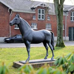 Lebensgrosse Bronzestatue vom erfolgreichen Holsteinerhengst Landgraf vor dem Gebäude der Reit- und Fahrschule Elmshorn.
