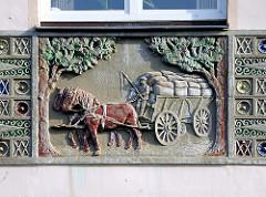 Dekorschmuck ein einer Hausfassade - Wohnhaus in Elmshorn, Mühlenstrasse; Kutscher mit Pferd und Wagen, beladen mit Säcken - Jugendstil.