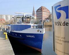 Hafen der Hansestadt Demmin - Fahrgastschiff Hamburg; Schild des WSV /  Wasser- und Schifffahrtsamt Stralsund - im Hintergrund Speichergebäude und Kirchturm der St. Bartholomaeikirche.