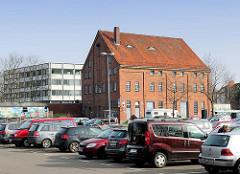 Blick über den Parkplatz Buttermarkt zur historischen Backsteinarchitektur der ehemaligen Markthalle in Elmshorn - das Gebäude war auch Teil der ehem. dort ansässigen Lederfabrik.