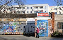 Geschäfte mit bunter Graffiti - Fussgängerin, Bilder aus der Hansestadt Rostock - Ortsteil Lichtenhagen.