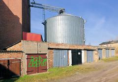 Metall-Silo im Hafen der Hansestadt Demmin - Reihe Garagen mit Holztoren.