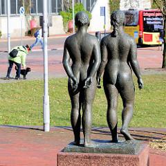 Bronzefiguren, zwei nackte Frauen, Rückansicht - im Hintergrund Bushaltestelle auf dem Theodor Heuss Platz in Itzehoe.