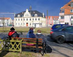 Sitzbank / Ruhebank an der Strasse, fahrende Autos; im Hintergrund das Rathaus der Stadt Demmin in Mecklenburg Vorpommern.