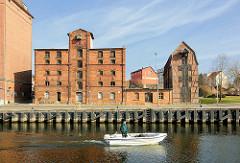 Blick über die Peene im Hafen der Hansestadt Demmin - historische Speichergebäude, Industriearchitektur - Backsteingebäude; ein kleines Motorboot fährt auf dem Fluss.