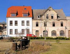 Restauriertes Wohnhaus, weisse Fassade -  rotes Ziegeldach neben einem leerstehenden verfallenene Wohnhaus - Bilder aus Bad Doberan; neu + alt.