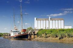 Kaimauer im Hafen von Itzehoe an der Stör - Schiff im Hafen, weisse Silos, blauer Himmel.