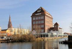 Ehem. Speichergebäude im Hafen der Hansestadt Demmin; umgebaut zum Geschäfts- und Bürogebäude; im Hintergrund mehrstöckige Plattenbauten und der Kirchturm der St. Bartholomaeikirche.