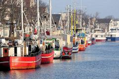 Warnemünde - Hafen am Alten Strom; rote Fischkutter / Fischereiboote am Kai; Häuser an der Vorreeg / Vordere Reihe.