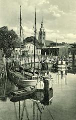Historische Aufnahme vom Hafen der Stadt Itzehoe an der Stör - Kirchturm der St. Laurenti-Kirche - Ewer, Lastsegler am Kai.