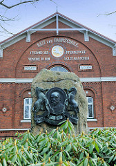 Denkmal Georg Ahsbahs vor der Fassade der Reit- und Fahrschule Elmshorn - Ahsbahs vereinigte 1891 die verschiedenen Pferdezüchtervereine zum Verband der der Pferdezuchtvereine in den Holsteinischen Marschen.