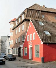 Einzelhaus mit roter Fassade neben mehrstöckiges Backsteingebäude, Wohnhaus in der Mühlenstrasse, Elmshorn.