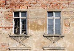 Fassade einer verfallenen Gewerbeimmobilie in der Hansestadt Demmin - abbröckelnder Putz, Ziegelsteine - verrottete Fenster.