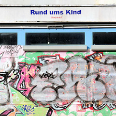 Geschäft mit heruntergelassenen Rollläden - bunte Graffiti / Laden in Rostock Lichtenhagen - Rund ums Kind, Barkauf.