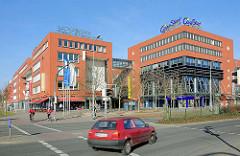 Neubau Rostock Lichtenhagen - Warnow Geschäftszentrum; rote Fassade - Strassenkreuzung.