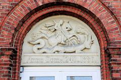 Reliefschmuck Eingang Hauptgebäude St. Jürgen Stift in Itzehoe. Sankt Jürgen ist die niederdeutsche Bezeichnung für den Heiligen St. Georg, der den Drachen besiegte.