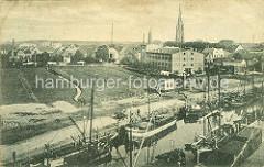 Historische Ansicht vom Hafen und der Stadt Elmshorn ca. 1919; das Ufer der Krückau ist dicht mit einer Flotte von Ewern belegt - im Hintergrund der Turm der St. Nikolaikirche.
