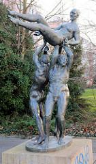 Bronzestatue Der Friede bewahrt das Leben, Bildhauer Bernd Göbel, 1980. Drei nackte Männer tragen eine nackte Frau - Kunst im Öffentlichen Raum / Rostock Lichtenhagen.