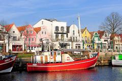 Roter Fischkutter im Hafen von Warnemünde / Alter Strom - historische Architketur, Wohnhäuser an der Promenade vom Ostseebad Warnemünde.