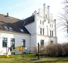 Historische Hausfassade - weisses Wohnhaus, Wäsche zum Trocknen in der Sonne - Pastorat in Elmenhorst / Lichtenhagen