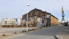 Backsteingebäude - alte Industriearchitektur, ehem. Neptunwerft Hansestadt Rostock; im Hintergrund Neubauten der Hafencity und stillgelegter Hafenkran.