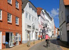 Moderne Ziegelfassade und Gründerzeitfassaden, verkehrsberuhigte Strasse in Rendsburg, Schleifmühlenstrasse - Fahrradfahrerin, Fussgänger.