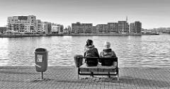 Hafenidylle im Rostocker Hafen - Sitzbank am Wasser; Architektur, Neubauten am Stadthafen / Schwarzweiss Fotografie.