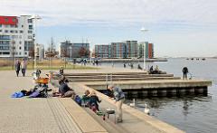 Uferpromenade am Rostocker Stadthafen, Hafencity - Besucher sitzen auf den Stufen, im Hintergrund Wohnhäuser am Wasser.