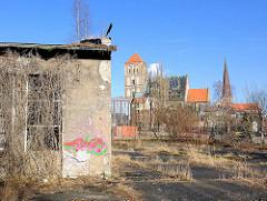 Verfallenes Lagergebäude - Güterbahnhof Rostock; im Hintergrund die Türme der Kirchen Nikolai + Petri.