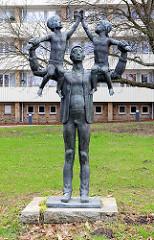 Vater mit zwei Kindern auf den Schultern / Bronzeskulptur in der Weststadt, Schwerin / Bildhauer Stephan Horota, 1976.