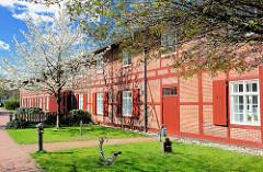Fachwerkgebäude, blühender Baum im Frühling - Arsenal in Rendsburg.