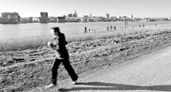Joggingstrecke an der Warnow / Unterwarnow; am anderen Warnowufer das Panorama der Hansestadt Rostock; Jogger im Lauf, langer Schatten der Morgensonne / Schwarz-Weiss Bild.