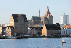 Speichergebäude an der Wasserseite Stadthafen Hansestadt Rostock - im Hintergrund die Marienkirche.