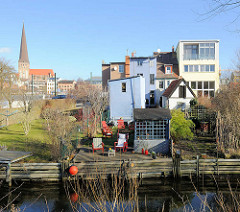 Wohnhäuser mit Garten an der Warnow - im Hintergrund die Rostocker Petrikirche.