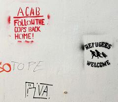 Grafitti - Wandmalerei auf einer weissen Hauswand in Rendsburg - REFUGEES WELCOME.