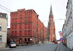 Historische Industriearchitektur / Backsteinarchitektur in Schwerin - Lagergebäude erbaut 1877; dahinter die neogotische Paulskirche - Einweihung 1869.
