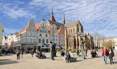 Historische Giebelhäuser am Neuen Markt in der Hansestadt Rostock; Möwenbrunnen - Künstler Waldemar Otto; im Hintergrund die Rostocker St. Marienkirche.