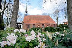 St. Johannes Kirche in Seester; Patronatskirche Kloster Uetersen; spätgotische Bau, Ursprung im 15. Jahrundert. Dachreiter mit kleiner Glocke - freistehender Glockenstuhl   aus Holz - blühender weisser Rhododrendron.