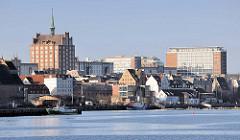 Wasserseite vom Stadthafen Hansestadt Rostock im Morgenlicht - Wohnhäuser am Wasser, Bürogebäude - lks. das Backsteinhochhaus an der Langen Strasse - Backsteingotik / Giebelhaus mit Kupferturm.