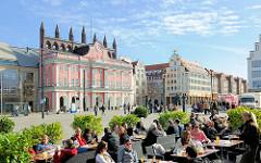 Neuer Markt Hansestadt Rostock - Aussengastronomie, Gäste an Tischen in der Sonne; Rathaus und historische Giebelhäuser.