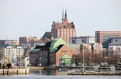 Blick über den Stadthafen Rostock - umgebautes Speichergebäude im Hafen - Theater im Stadthafen - Volkstheater; im Hintergrund Backsteinhochhaus in der Rostocker Innenstadt.