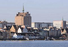 Panorama der Wasserfront vom Rostocker Stadthafen - mehrstöckige Wohnhäuser - Backsteinhochhaus mit Kupferturm an der Langen Strasse - ein Wahrzeichen von Rostock.