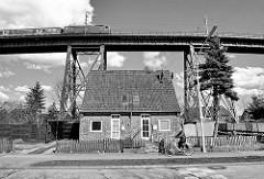 Einfaches Backstein-Wohnhaus mit Spitzdach unter der Eisenbahnhochbrücke von Rendsburg - Schwarz Weiß Aufnahme.