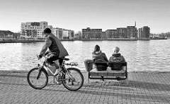 Stadthafen Hansestadt Rostock - im Hintergrund Neubauten, Wohnhäuser moderne Architektur der sogen. Hafencity - zwei Frauen auf einer Bank am Wasser / Radfahrer.