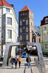 Metallbrücke über eine Brunnenanlage, Fussgänger; Kirchturm der St. Nikolaikirche Rostock.