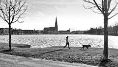 Schwarz-Weiss Aufnahme; Fusgänger mit Hund am Pfaffenteich in Schwerin - im Hintergrund der Schweriner Dom.