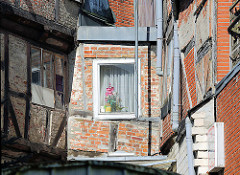 Hinterhof in Rendsburg - moderner Fensterrahmen, altes Fenster im Fachwerkhaus - Balkeninschrift: WER GOTT ZUM FRENDE HAT DARF SICH FÜR NIEMAND SCHEUEN.