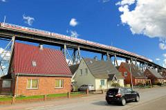 Einfamilienhäuser mit Spitzdach, Eisenbahnhochbrücke mit Personenzug - Fotos aus Rendsburg, Schleswig-Holstein.