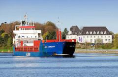 Leerer Container Frachter / Feeder ABIS CARDIFF auf dem Nord-Ostsee-Kanal in Rendburg - im Hintergrund das Gebäude des Instituts für berufliche Aus- und Fortbildung IBAF.